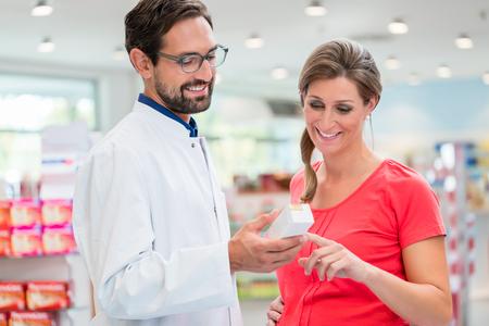 Zwangere vrouw winkelen in drug store wordt geadviseerd door sales man
