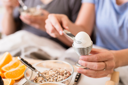 cereals holding hands: Woman opening a boiled egg in an eggcup for breakfast using a knife with selective focus to her hands
