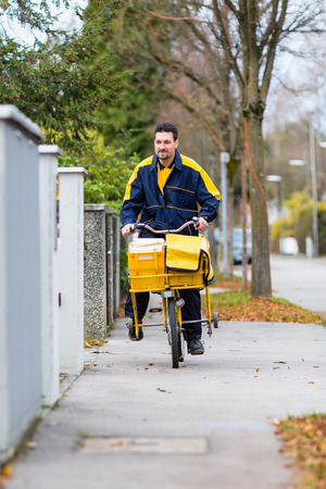 postal: Postman riding his cargo bike carrying out mail in neighborhood Stock Photo