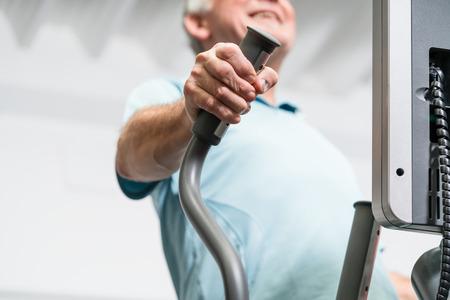 Elderly man training on cross trainer at the gym