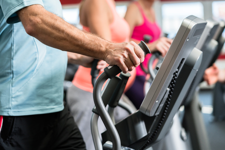 Seniors train on cross trainer with personal trainer at the gym Banco de Imagens - 65579267