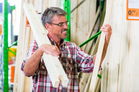 construction materials: Customer in lumber department of hardware store choosing wood strip for DIY-project