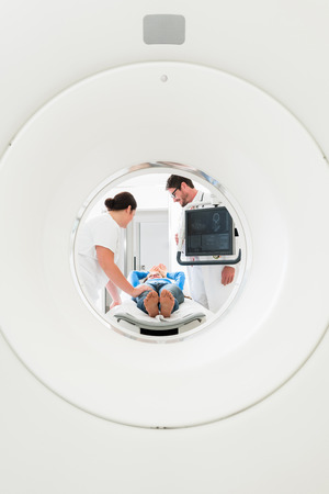 computer tomography: Doctor, nurse, and patient at CT scan tomography in hospital, shot through the tube of device