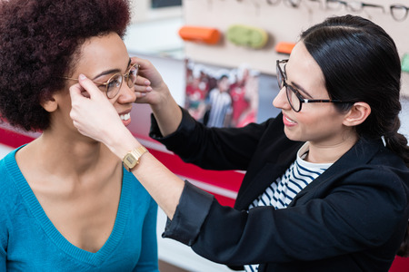 specs: Optician showing woman new glasses and handing them to her Stock Photo