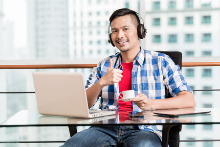 Young asian professional in skyscraper office having coffee and giving the thumbs up sign Stock Photo