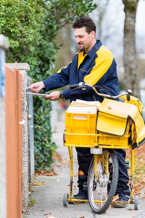 addressee: Postman delivering letters to mailbox of recipient Stock Photo