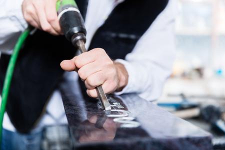 Artisan travaillant avec burin pneumatique à la pierre tombale Banque d'images