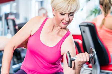 Mujer mayor de trabajo con pesas en el gimnasio