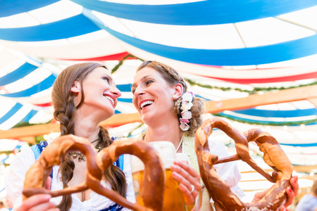 Two friends wearing dirndl are standing in a beer tent at Dult or Oktoberfest with giant pretzels