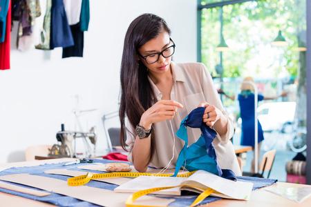 アジアのファッション ・ デザイナーの女性彼女のワーク ショップで縫製