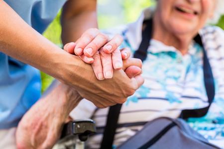 看護師の彼女の手を握って慰めの年配の女性