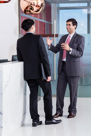 front desk: Asian executive Manager and affiliate leaning at front desk of office building and talking about business