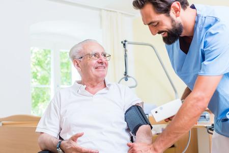 Verpleegster meten van de bloeddruk van senior patiënt
