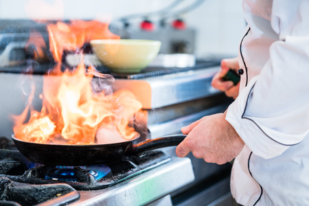 pan: Chef doing flambe to dish in pan with large fire flame