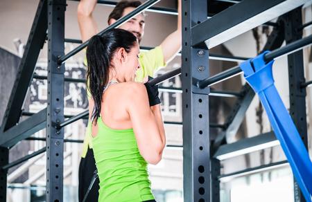 Le donne e l'uomo di formazione in gabbia per una migliore forma fisica, come gruppo