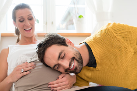 Soon-to-be Dad listening at belly of his pregnant wife for motions of embryo