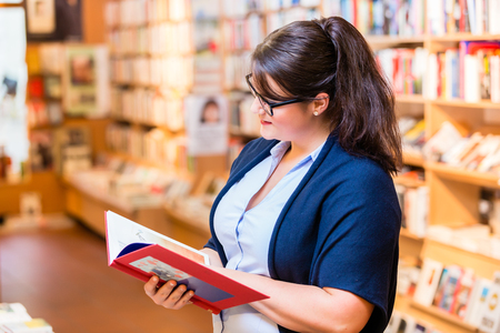 buying: Woman buying books in bookstore