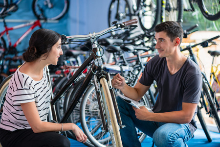 Couple looking for bicycle in bike shop Stock Photo - 64982012