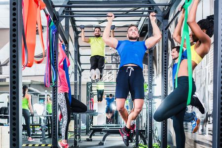 Groep van vrouwen en mannen in de kooi bij fitness sport oefening in de sportschool Stockfoto