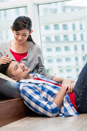 highriser: Asian girl caressing her boyfriend lying exhausted on the ground