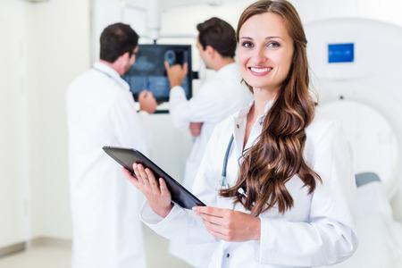 resonancia magnética: Doctor con los colegas de pie en el hospital en la máquina de TC con los resultados del análisis