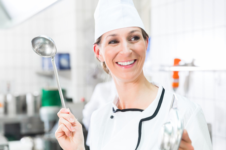 Smiling chef in commercial kitchen waving ladle