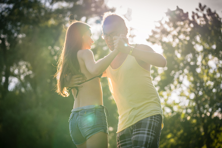 mann: Mann turning woman while dancing Bachata in the sun Stock Photo