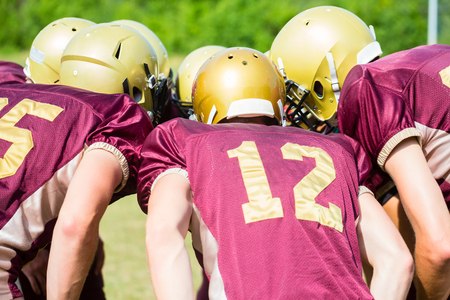 American Football players at strategy huddle Stock Photo - 64982035