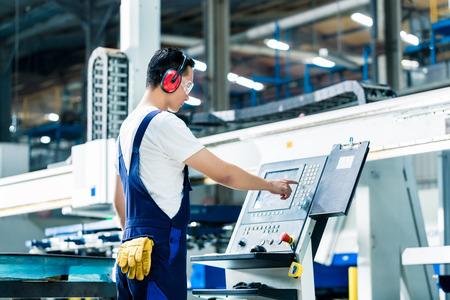 Trabajador introducción de datos en la máquina CNC en planta de la fábrica para obtener la producción va