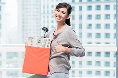 highriser: Young asian girl carrying moving box in front of window to city skyline