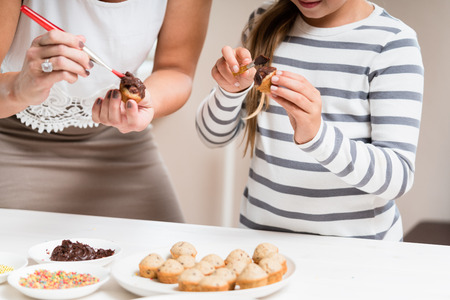 mommy: Pregnant mum and her little daughter baking together and decorating the cupcakes