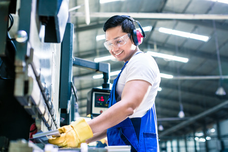 Asian worker in factory at metal skip machine putting work piece in