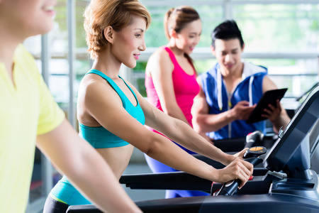 Computer instruction: Group of sportive young people during cardio training on treadmill under supervision of trainer with tablet Stock Photo