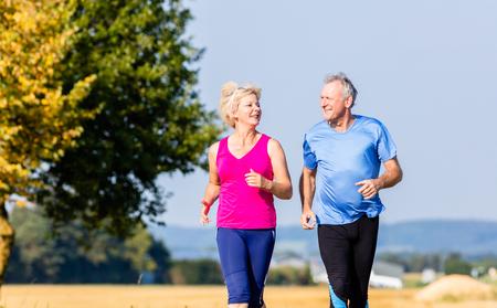 Senior woman and man running doing fitness exercises Stock Photo - 64982073