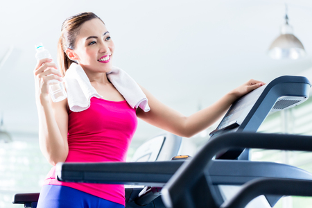 sufficient: Smiling young woman on treadmill presenting water bottle as a reminder of sufficient hydration during workout