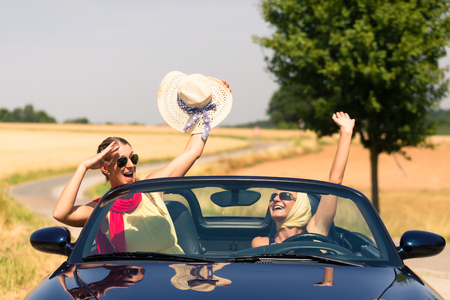 joyride: Best friends having summer joyride in convertible car passing a field