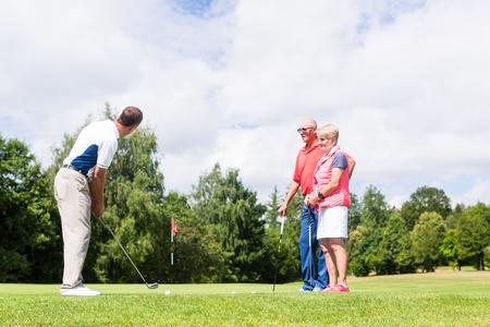 grupo de hombres: Favorable de golf practicando el deporte con la mujer mayor y un hombre