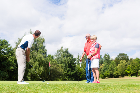woman golf: Golf pro practicing the sport with senior woman and man