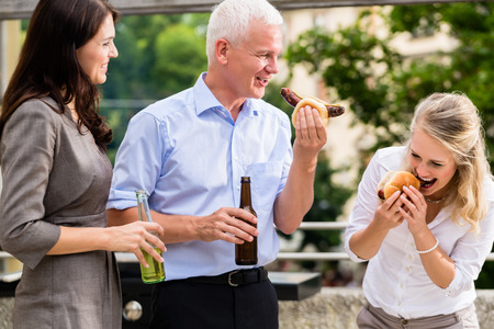 Colleagues having sausages and beer after work Stock Photo