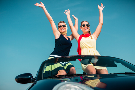 cabrio: Woman having summer trip in convertible car stretching hands in the air with fun