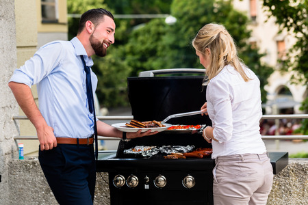 fun at work: Office colleagues grilling sausages at bbq after work on terrace