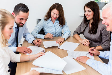 negotiating: Lawyers having team meeting in law firm reading documents and negotiating agreements