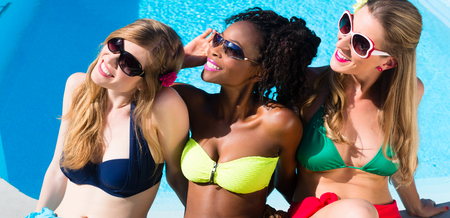 afroamerican: Diversity girls sitting on swimming pool in summer relaxing, African and Caucasian girls