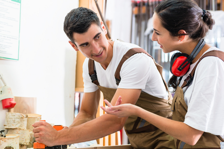 Carpenter team of woman and man working together Stock Photo