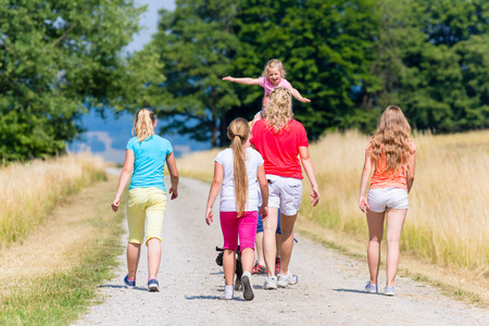 and hiking path: Family, mother father and kids, having walk in summer on dirt path