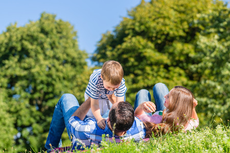 family playing: Family playing with son lying in grass on meadow