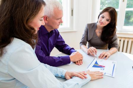 Ältere Frau und Mann im Pensionsfinanzplanung mit dem Berater oder Berater
