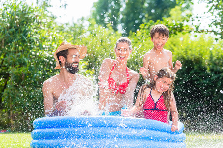 Family in garden pool splashing water cooling down, mother, father and kids having fun together
