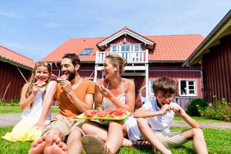 home and garden: Family, house, fruit, healthy, home sitting, mother, mom, woman, eating, melon, water melon. fresh, together, grass, meadow, boy, child, kid, children, father, dad, man, girl, siblings, parents, garden, grass, summer, rural, village, enjoying, suburb,   Stock Photo