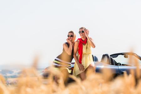 Women having joyride in convertible car having rest at grain field enjoying the landscape Stock Photo